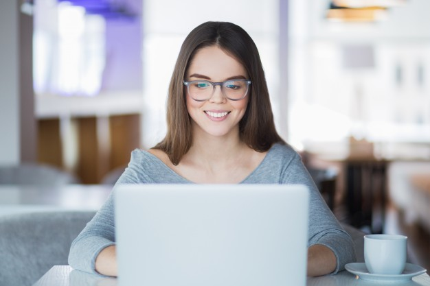 woman with glasses smiling while using a laptop
